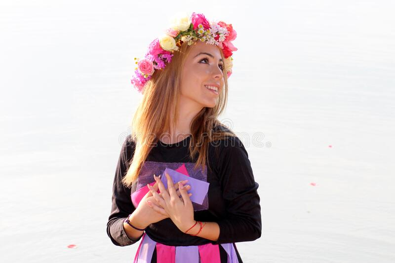 Woman in Black Purple and Pink Long Sleeve Dress and Pink Yellow and Beige Rose Headdress stock images