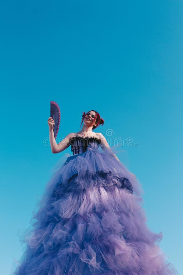 Woman in Black and Purple Ruffle Dress Holding Hand Fan stock photography