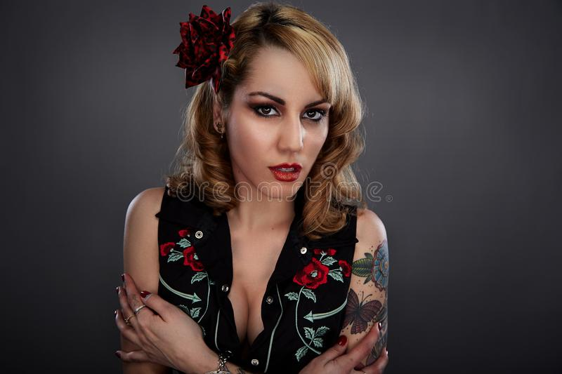 Woman in Black Red and Green Floral Sleeveless Shirt With Red Flower on Her Head and Butterfly Tattoo on Her Left Arm stock images