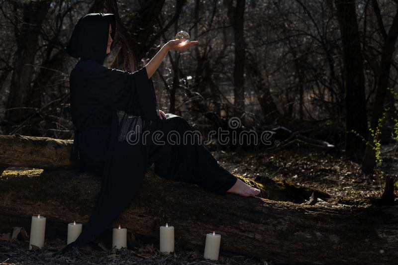 Woman in black robes surrounded by burning candles is sitting on a tree trunk in the forest and holding clear crystal ball stock photos