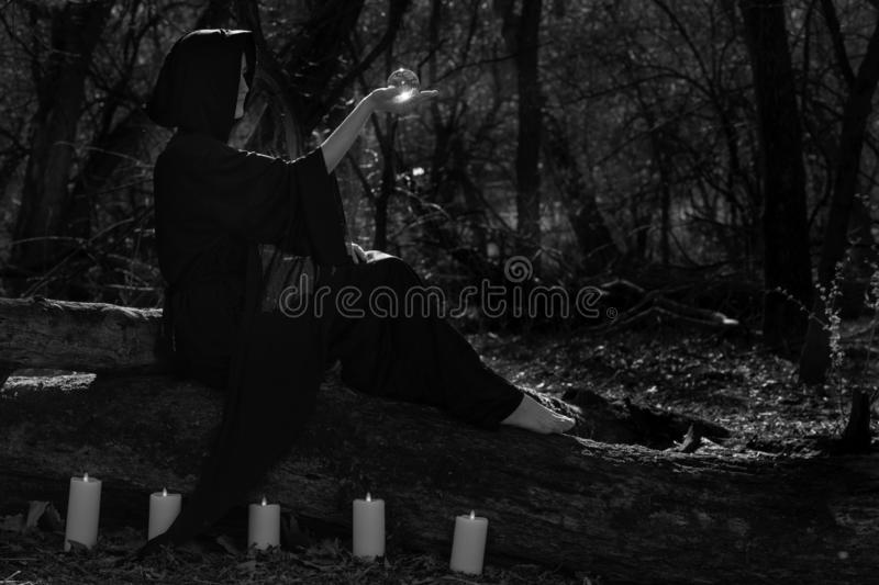 Woman in black robes surrounded by burning candles is sitting on a tree trunk in the forest and holding clear crystal ball royalty free stock photos