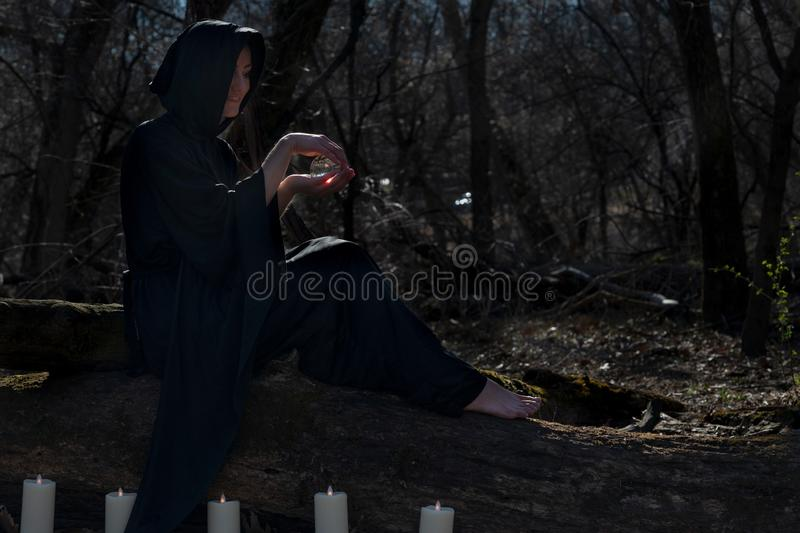 Woman in black robes surrounded by burning candles is sitting on a tree trunk in the forest and holding clear crystal ball stock image