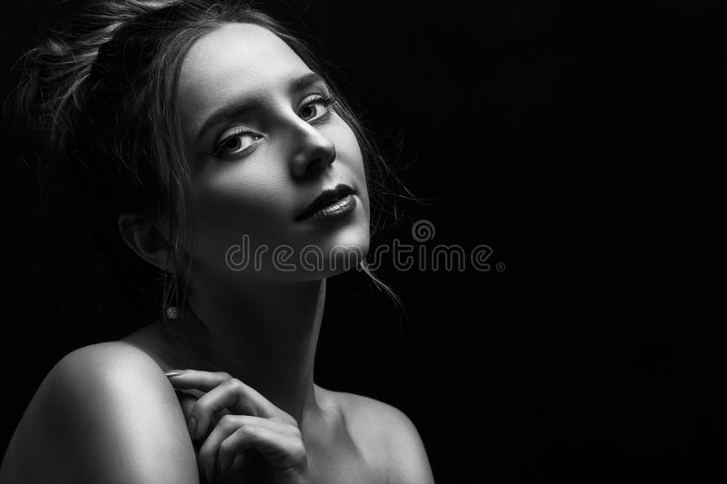 Woman on black. Sensual woman on black background with copy space looking at camera, monochrome royalty free stock images