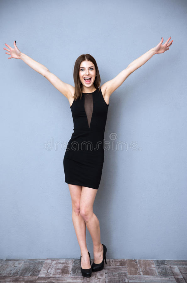 Woman in black dress greeting you. Happiness young woman in black dress greeting you stock image