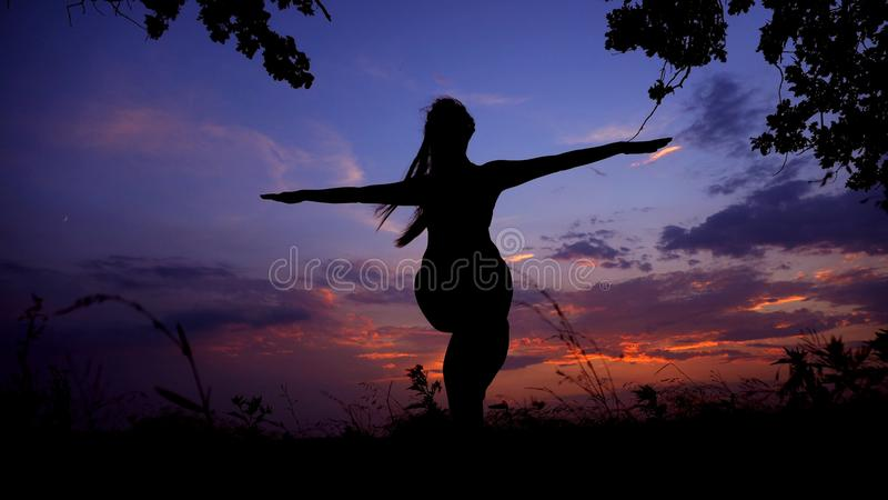 Woman black shadow silhouette in evening sky background, yoga asana. Concept of eastern practise and relaxing before night stock image