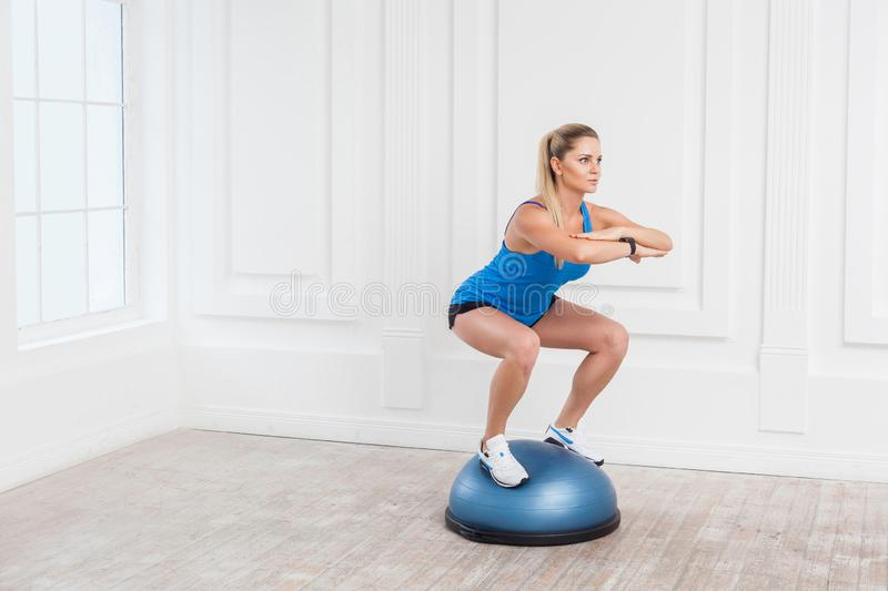 Woman in black shorts and blue top working in gym doing exersice in bosu balance trainer, squats on fitness ball, holding balance. Portrait of concentration stock photos