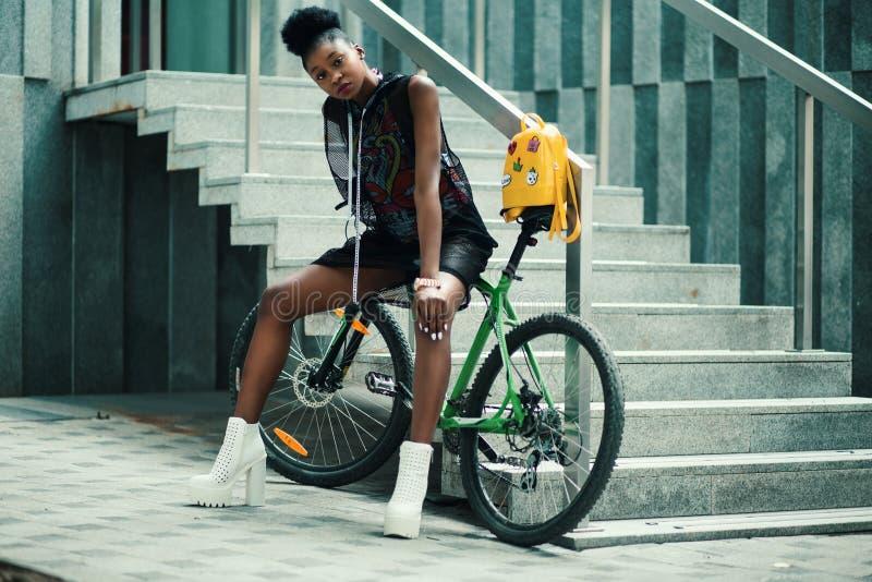 Woman in Black Sleeveless Dress Sitting on Green Bike royalty free stock image