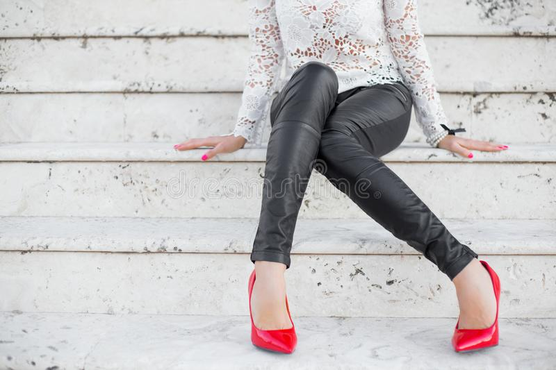 Woman in black slim pants and red heels sitting on stairs royalty free stock image