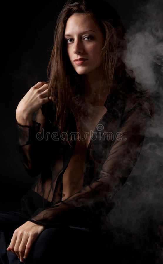 Woman in Black With Smoke. A dramatic image of a gorgeous woman in a sheer black top against a black background with smoke floating around her royalty free stock photography