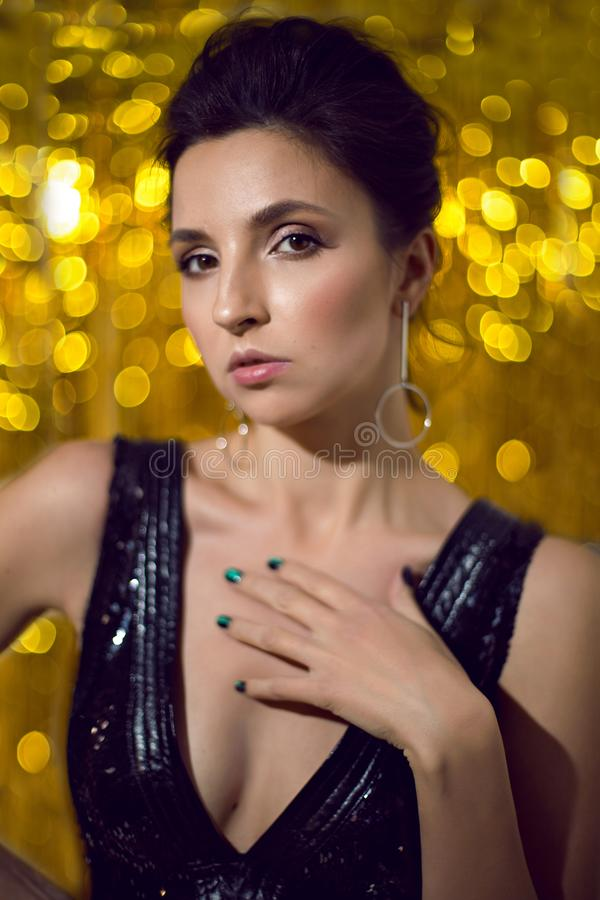 Woman in the black sparkly dress made of sparkles is in Studio royalty free stock photo