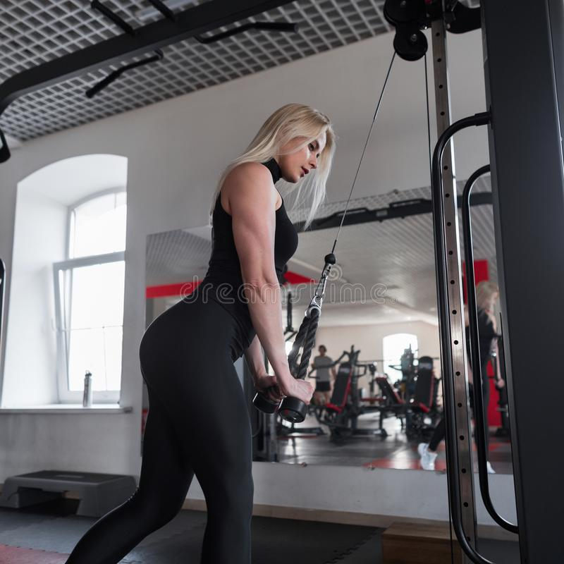Woman in black sportswear is training in the gym. The concept of beauty and health stock image