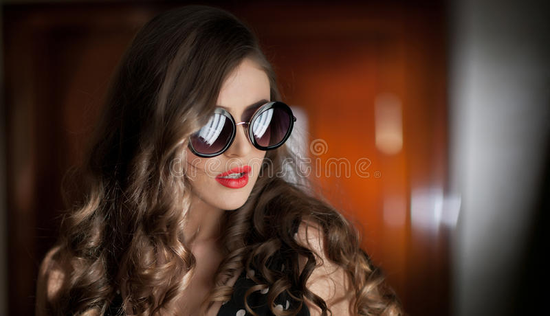 Woman with black sunglasses and long curly hair. Beautiful woman portrait. Fashion art photo of young model with sunglasses. Elegant female portrait isolated royalty free stock photo