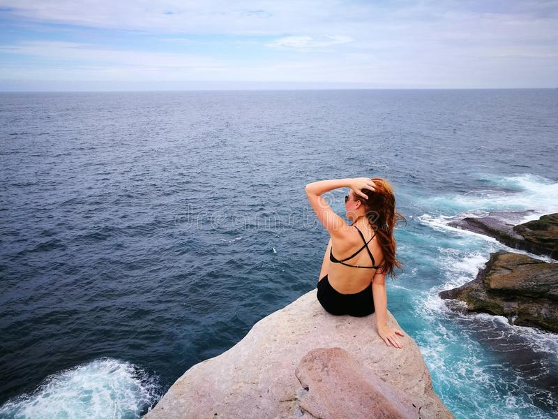 Woman in Black Swimwear Set Sitting on Top of Gray Rocky Cliff Facing Body of Water royalty free stock image