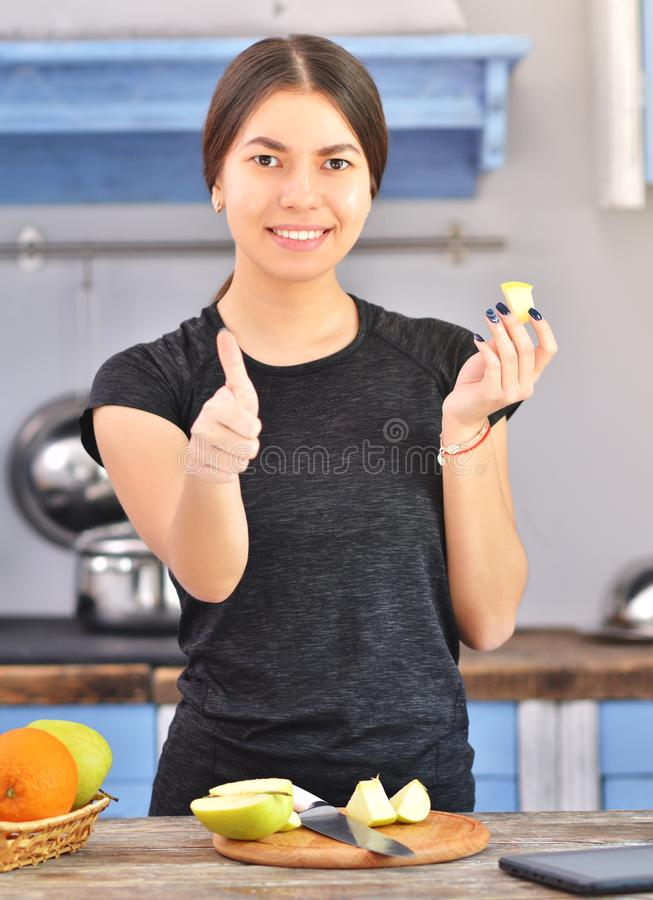 A woman in a black t-shirt makes a fit breakfast. And tries to taste a piece of apple, superfood, beauty, dieting, knife, delicious, healthy, lifestyle stock photo