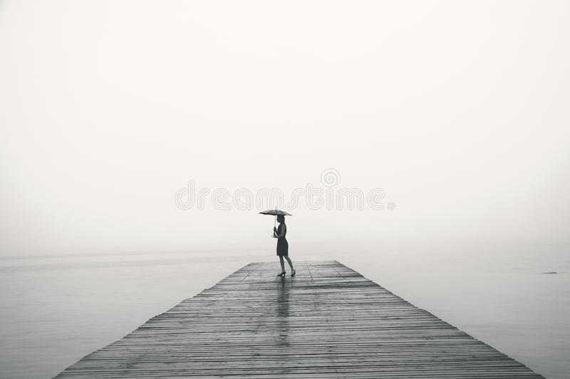 Woman with black umbrella looking infinity in a surreal place royalty free stock photos