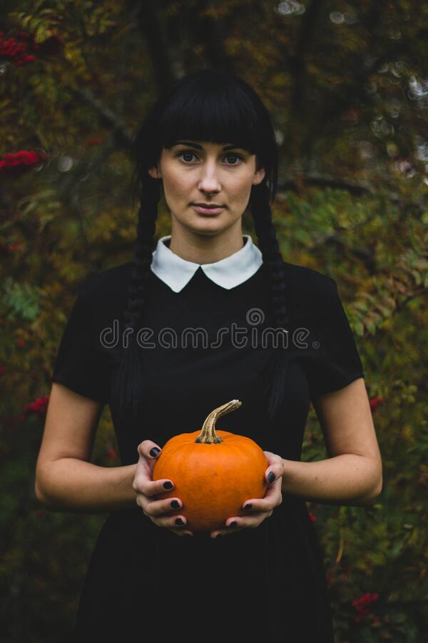 Woman in Black and White Collared Dress Holding Pumpkin during Daytime stock photo