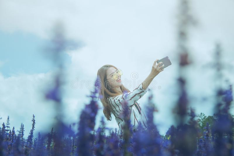 Woman in Black and White Dress Shirt Taking Photo on Lavender Flower Field at Daytime stock photo