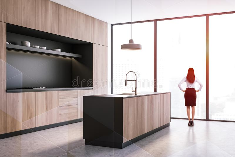 Woman in black and wooden kitchen stock photo