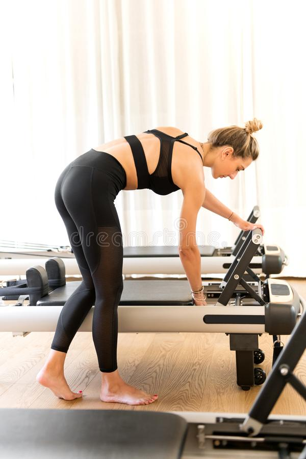 Woman in workout clothes adjusting reformer pilates bed royalty free stock image