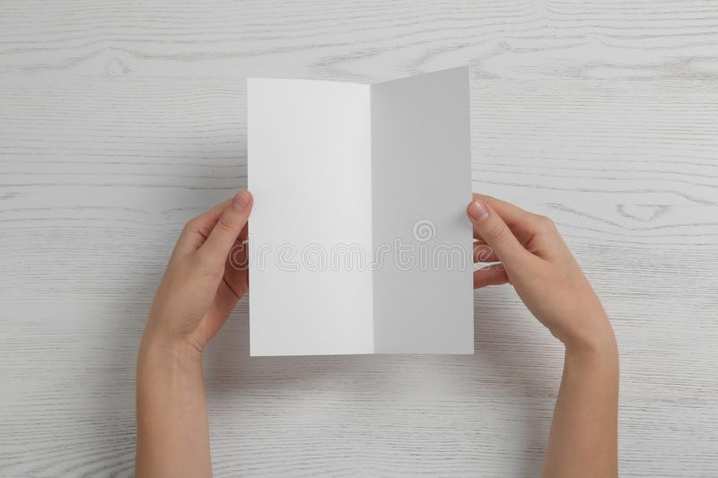 Woman with blank brochure on wooden background, above view. stock photos