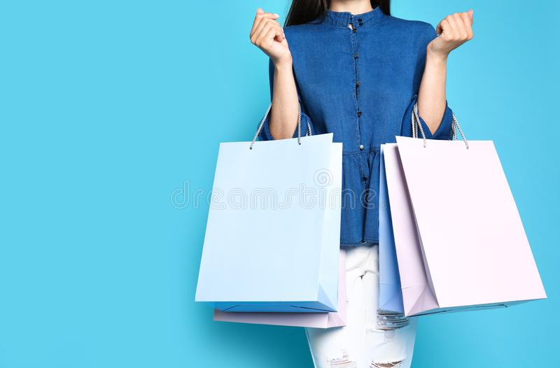 Woman with blank paper bags against color background, closeup. Space for text stock photography