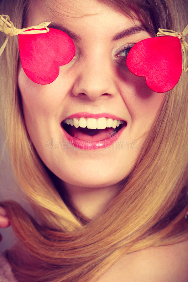 Woman blinded by her love. Love and happiness concept. Cheerful enjoyable young female with little small hearts on sticks covering woman eyes. Lovers blinded by stock photo