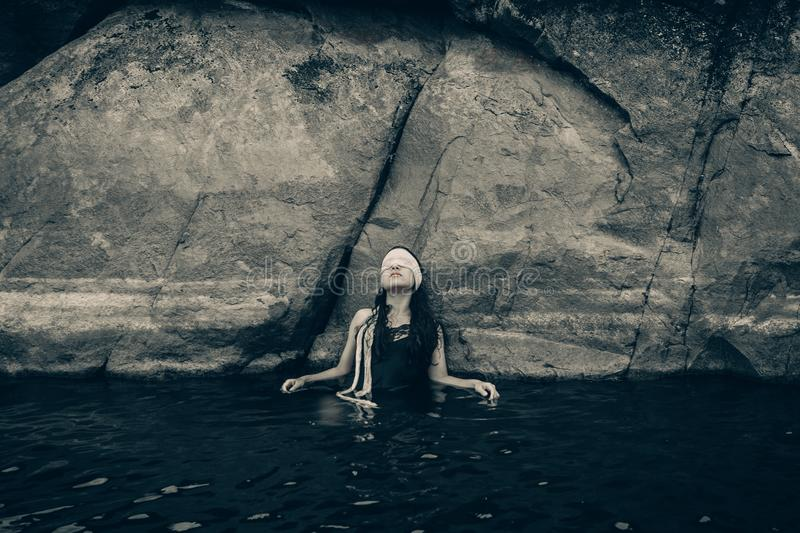 Woman in Blindfold Wearing Black Top on Body of Water While Leaning on a Rock stock photo