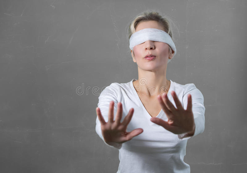 Woman blindfolded with hands reaching forward stock photos
