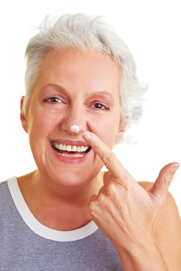 Woman with blob on her nose. Happy senior woman applying lotion to her face royalty free stock images