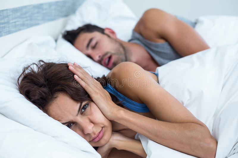 Woman blocking ears with hands while man snoring on bed royalty free stock photography