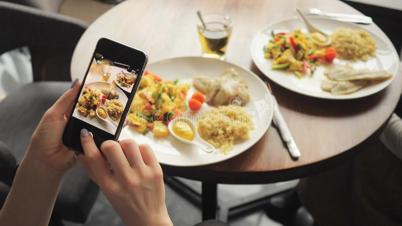 Woman blogger takes pictures of her food in a cafe using mobile phone. royalty free stock photos