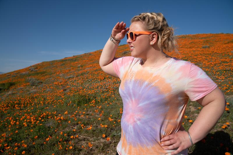 Woman with blond braided hair looks off into the distance in the poppy field during a super bloom royalty free stock photo