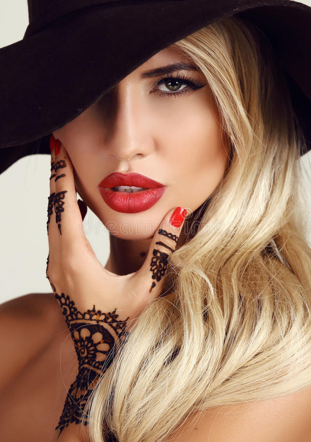 Woman with blond hair with evening makeup and henna tattoo on hands. Fashion studio portrait of beautiful sensual woman with blond hair with evening makeup and stock photo
