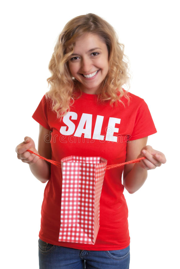 Woman with blond hair in a sales-shirt holding a shopping bag. On an isolated white background for cut out stock images