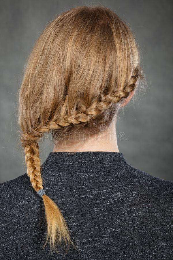 Woman with blonde hair and braid hairdo. Hairstyles and hairstyiling concept. Woman with dark blonde hair and braid hairdo, back view. Studio shot on dark royalty free stock images