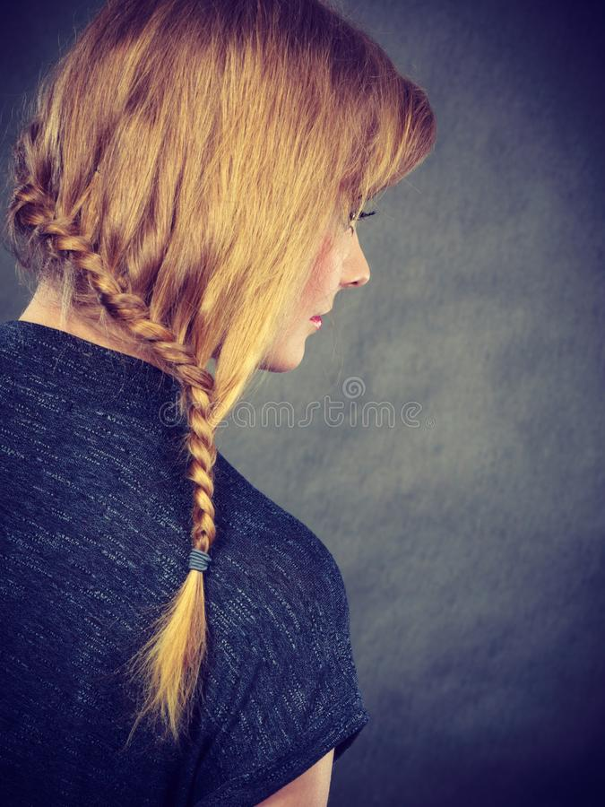 Woman with blonde hair and braid hairdo. Hairstyles and hairstyiling concept. Woman with dark blonde hair and braid hairdo, back view. Studio shot on dark stock images