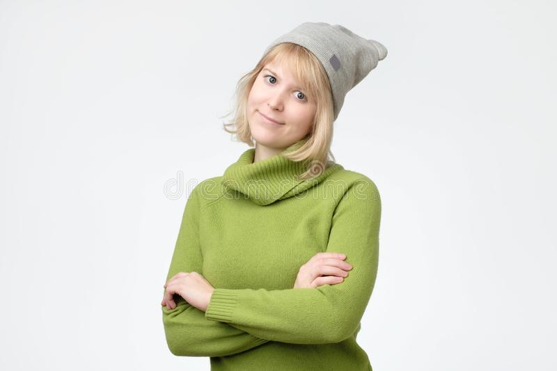 Woman with blonde hair and green sweater smiling gently while listening to interesting conversation. Beautiful young woman with blonde hair and green sweater stock photos