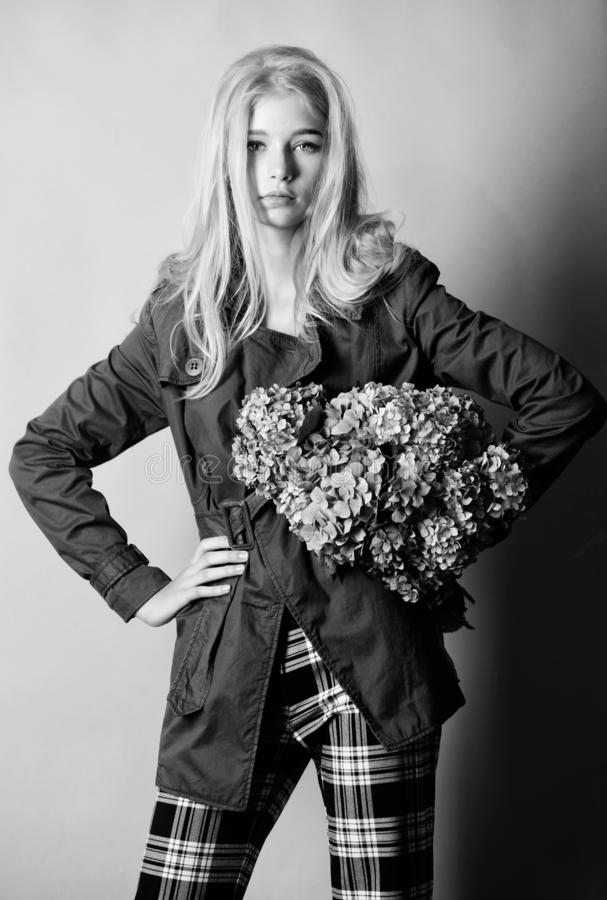 Woman blonde hair posing coat with flowers bouquet. Clothes and accessory. Girl fashion model wear coat for spring and. Autumn season. Trench coat fashion trend stock image