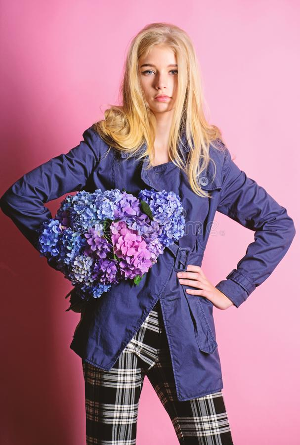Woman blonde hair posing coat with flowers bouquet. Clothes and accessory. Girl fashion model wear coat for spring and. Autumn season. Trench coat fashion trend royalty free stock images