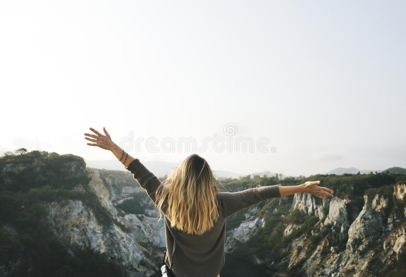 Woman With Blonde Hair at the Top of the Mountain Raising Her Hands stock photo
