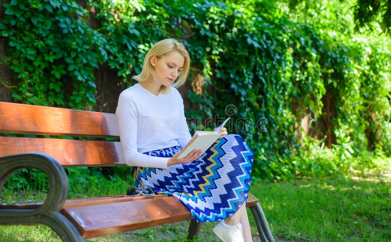 Woman blonde take break relaxing in park reading book. Reading literature as hobby. Books are her passion. Girl keen on royalty free stock photo