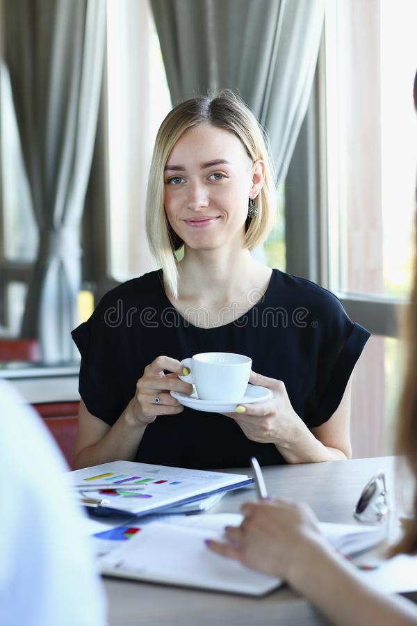 Woman blonde talking to friends in a cafe royalty free stock photography