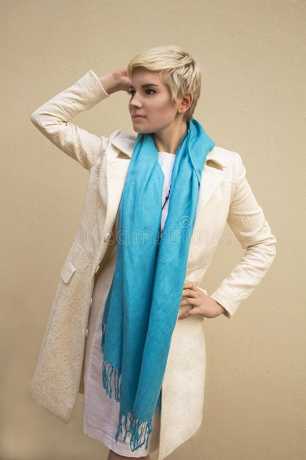 Woman blonde in white coat, blue scarf. Fashion hairstyle, make-up. royalty free stock images