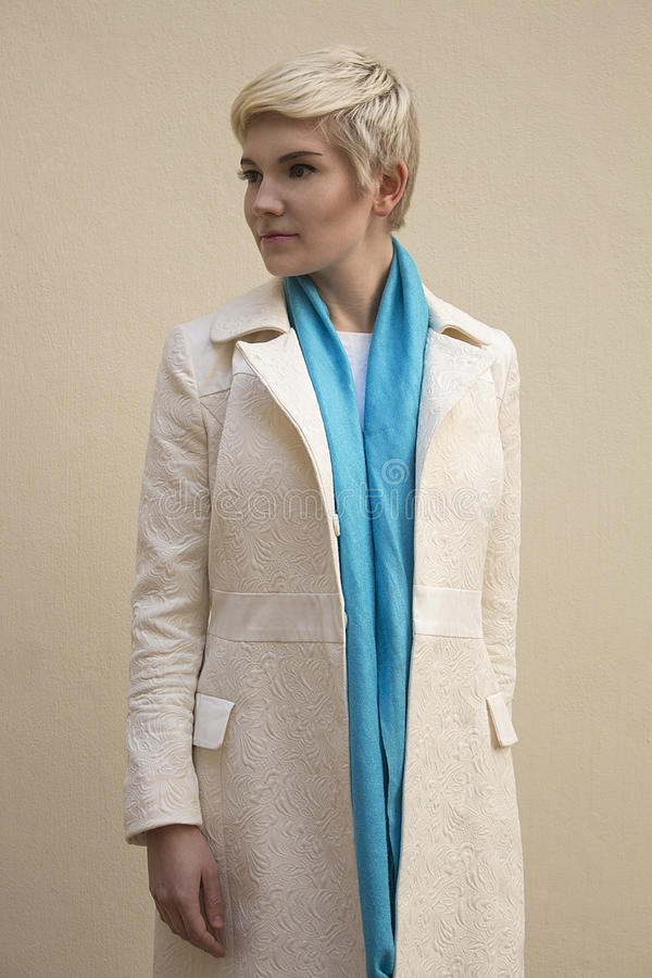 Woman blonde in white coat, blue scarf. Fashion hairstyle. stock images