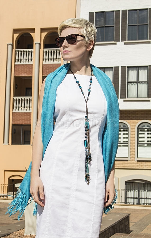 Woman blonde in white dress, coat, blue scarf. Fashion hairstyle. stock photo