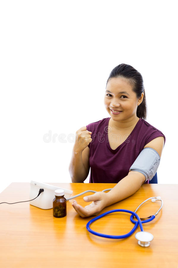 Woman with blood pressure test. Young adulte woman happy with her self blood pressure test (Selective focus at woman royalty free stock photo