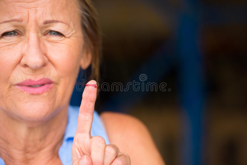 Woman bloody cut finger wound. Portrait stressed woman in pain, hurt and suffering, close up of tissue on injured, cut bloody finger wound stock images