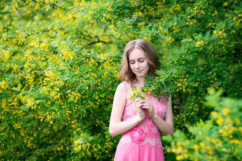 Woman in blooming yellow summer garden. Model stock photos