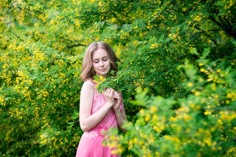 Woman in blooming yellow summer garden. Model royalty free stock photos