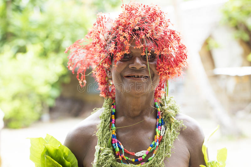 Woman blossoms on head Solomon Islands. Funny costumed woman with blooming flower on head waiting to celebrate the typical dances royalty free stock images